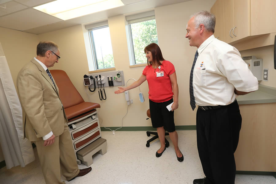 Deputy Minister Dr. Peter Vaughan, Minister Leo Glavine and nurse Sheila Lee tour the renovated Queens General Hospital.