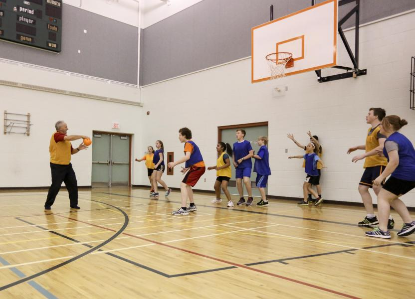 Minister Glavine plays a game of hand ball with the students of Pine Ridge Middle School.