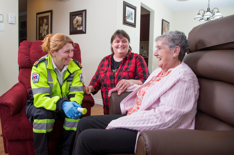 A palliative care patient has a visit from paramedics in her home to assist in her home care