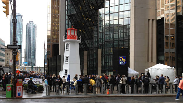 Torontonians listen to speakers at a promotion at the Peggy's Cove lighthouse installation at the corner of Bay and Wellington streets in downtown Toronto.