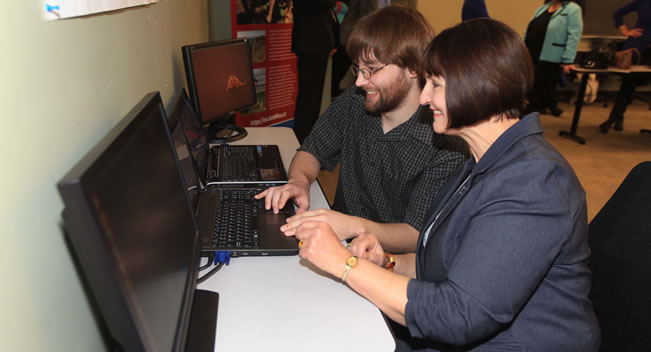 Colibri software developer Alex Sanford showing Education Minister Ramona Jennex the new software at a computer.