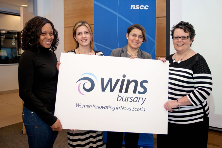 FROM RIGHT: Joanne Bernard, Minister responsible for the Advisory Council on the Status of Women, stands with May Farouk, Amanda Hickey and Jalana Morton hold a sign for the council's annual bursaries.