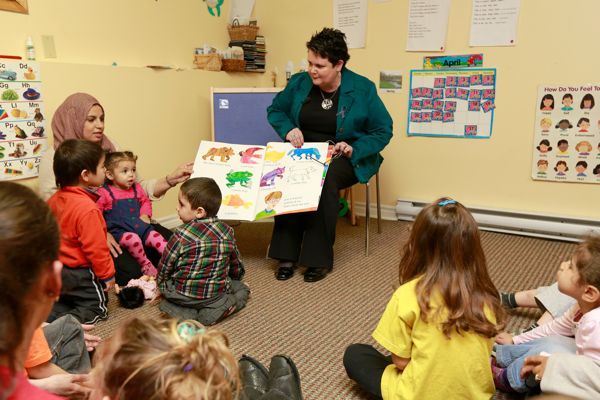 Community Services Minister Joanne Bernard sits on a chair, reading a large picture book to children and parents at the Dartmouth Family Centre.