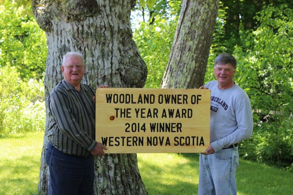 Hiram and Ernest Carver hold an award for the Provincial and Western Region Woodland Owners of the Year.