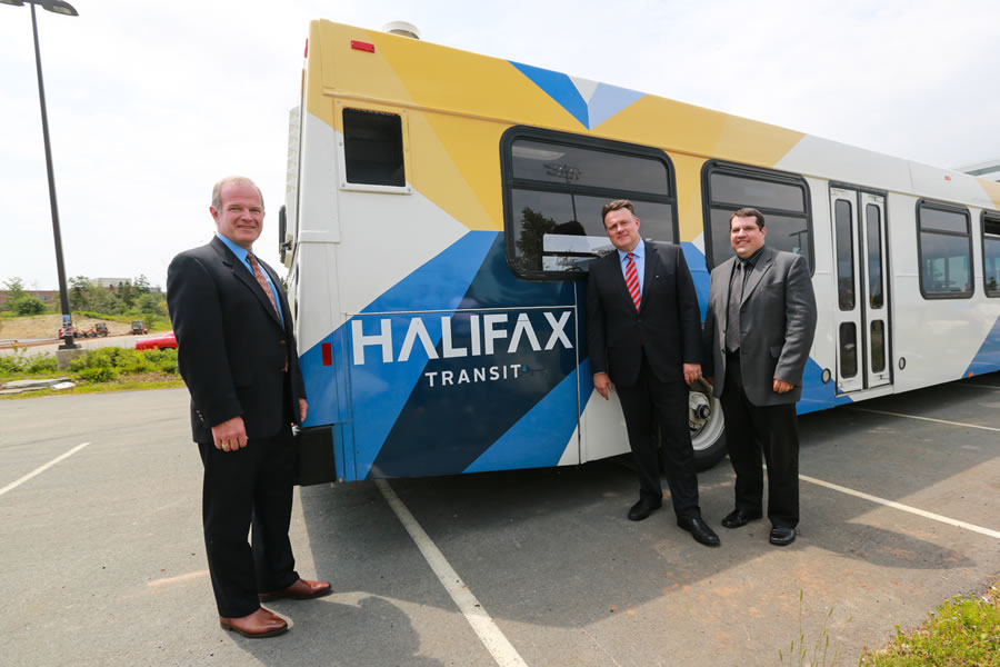 Municipal Affairs Minister Mark Furey, Halifax Mayor Mike Savage & Eddie Robar of Halifax Transit pose in front of a newly rebranded city bus.