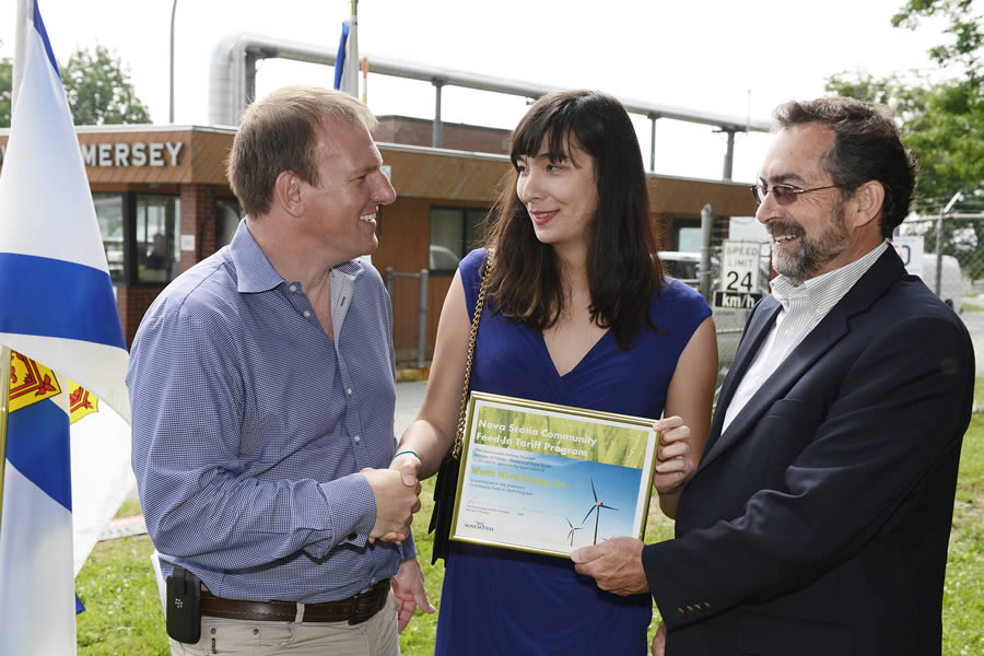 Energy Minister Andrew Younger shakes hands with Danielle Fong, LightSail Canada's co-founder and chief scientist, as Stan Mason from Watts Wind looks on in front of the former Bowater Mersey mill.