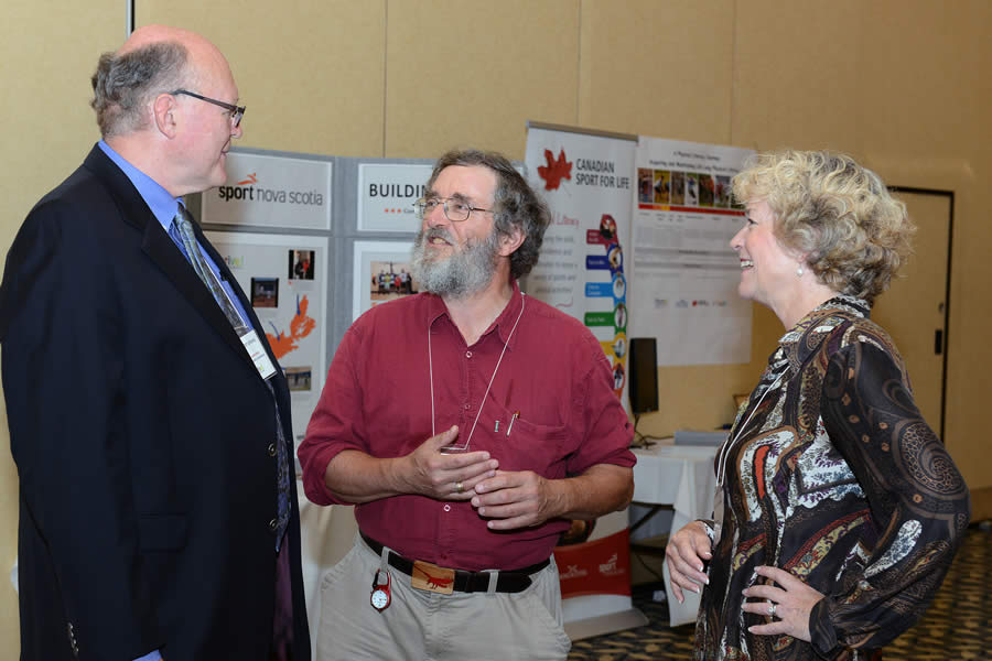 Dr. Robert Strang, Nova Scotia's chief public health officer, chats with keynote speakers Dr. Trevor Hancock and Brenda Zimmerman.