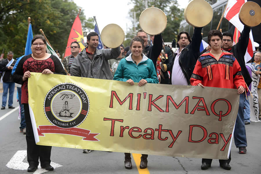 Three Mi'kmaq youth hold a banner as they lead the march celebrating Treaty Day