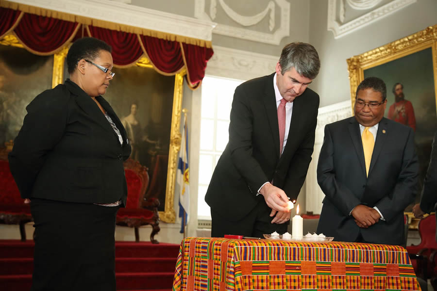 Tracey Dorrington-Skinner of VOICES and Minister of Communities, Culture and Heritage Tony Ince look on as Premier Stephen McNeil lights a candle as part of the formal apology.
