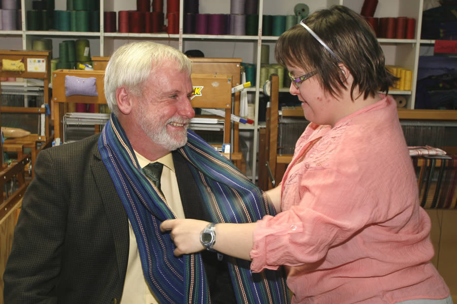L'Arche Homefires client Kristy puts a scarf she weaved around Kings South MLA Keith Irving at the Appleworks Building in Wolfville.