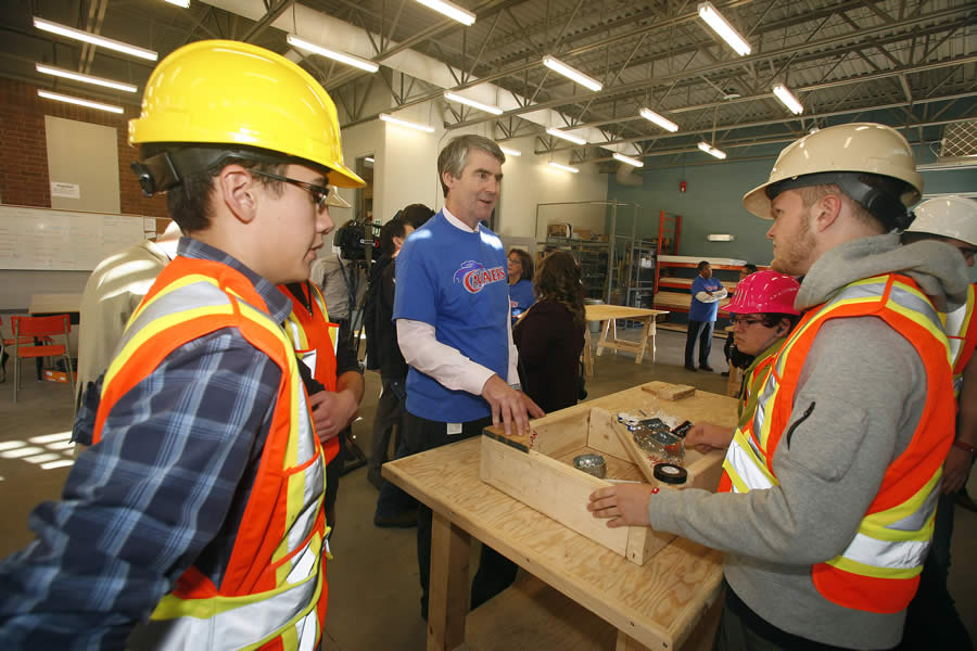 Premier McNeil talks with three students working on a project in the skilled trades centre at Cole Harbour District High School