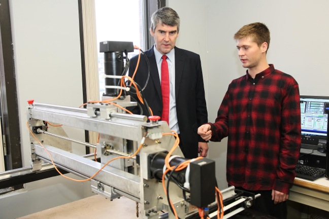 Dalhousie engineering grad Andreas Hart shows Premier Stephen McNeil the computer-controlled mill he invented to make surfboards.