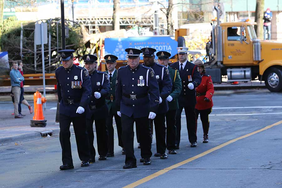 An honour guard of Halifax Regional Police, Halifax Regional Fire and Emergency, Department of Natural Resources Enforcement and Royal Canadian Mounted Police, lead the tree out of the city.
