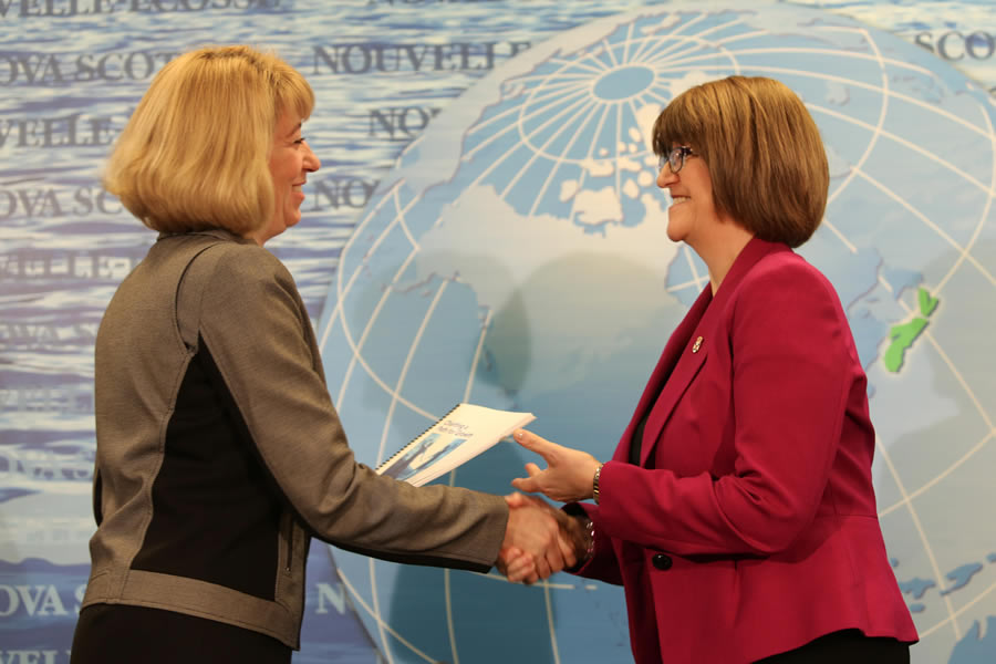 (From left) Laurel Broten, who wrote the report, gives a copy to Finance and Treasury Board Minister Diana Whalen.