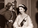 Princess Elizabeth, wearing white evening dress and blue ribbon of order of the garter and diamond tiara and necklace, and Duke of Edinburgh, in evening clothes and order of the garter, walk through corridor of the Nova Scotian Hotel.