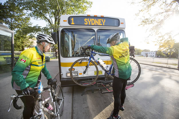 Two cyclists place their bikes in a rack on the front of a bus.