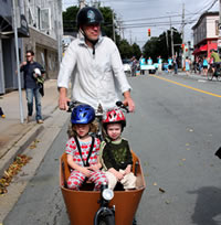 Man on a large bike with two kids in a front carrier