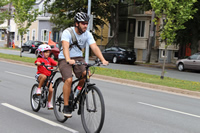 Man riding a bike with a child in a carrier